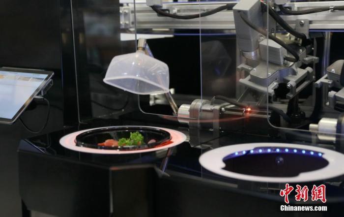 """当地时间8月20日,一台机器人厨师正在做菜。随着俄罗斯新冠病毒疫情的持续,莫斯科餐馆的""""机器人厨房""""颇受欢迎。近日莫斯科一家叫做""""许多三文鱼""""的连锁餐厅在自己的一家门店里安装了一台机器人厨师。这是一台体型庞大的""""家伙"""",可同时做四份菜。顾客可通过操作面板来点餐,机器人则会按照程序,将提前配好的菜依次放入盘中,再配上酱汁,整个过程顾客只要等候几分钟,也不需要和服务员接触。 <a target='_blank' href='http://www.chinanews.com/'>中新社</a>记者 王修君 摄"""