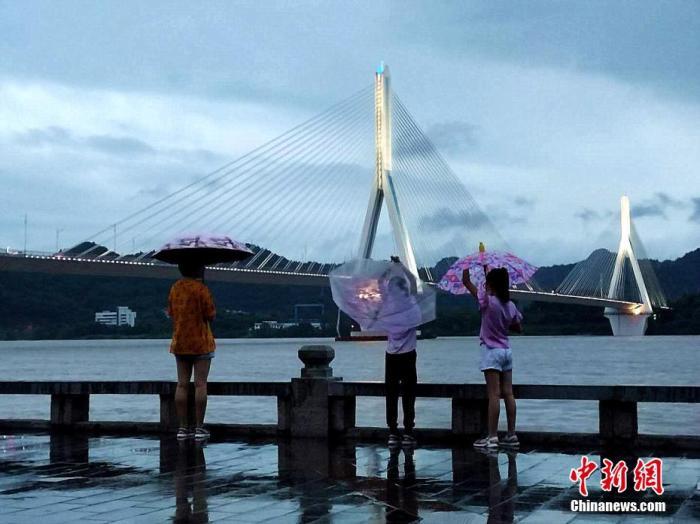 """8月20日,""""长江2020年第5号洪水""""过境湖北省宜昌市,当地不少市民来到江边查看水情。受近期强降雨影响,长江上游干流及岷江、沱江、嘉陵江等共计62条河流发生超警以上洪水,三峡水库入库流量当天涨至75000立方米每秒,这是三峡水利枢纽自2003年建库以来遭遇的最大洪峰。当天上午10时,宜昌水位达53.29米,超警戒水位0.29米。吴延 摄"""