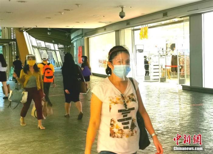 资料图:菲律宾市民佩戴各款口罩加面罩,经过菲律宾首都马尼拉CBD马卡蒂绿带商圈。<a target='_blank' href='http://www.chinanews.com/'>中新社</a>记者 关向东 摄