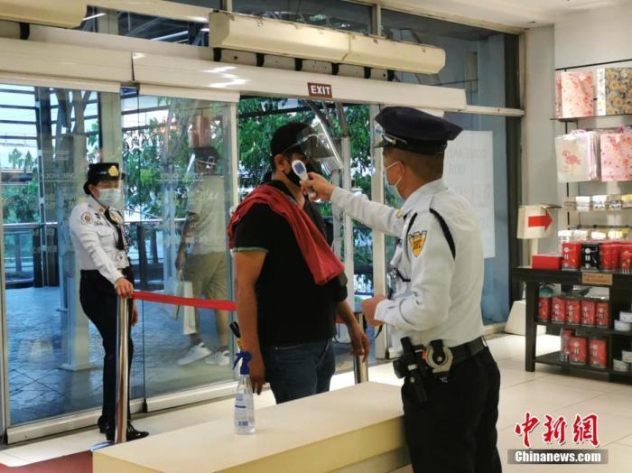 8月22日,马尼拉CBD马卡蒂LANDMAK商场,保安为戴面罩的顾客量体温。菲律宾新发传染病管理跨机构工作组要求,人们在公共交通、工作场所,以及所有封闭的场所,均须戴面罩。 中新社记者 关向东 摄