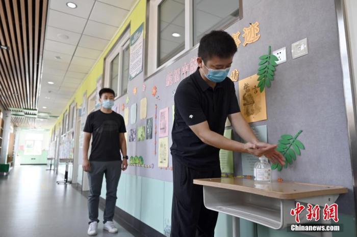 8月24日,北京教育学院附属丰台实验学校,教职员工进入教室前进行手部消毒。该校所有教室门口都摆放了消毒液等防疫用品,在新学期开学后供学生使用。当日,北京市委教育工委副书记、市教委新闻发言人李奕表示,新学期,北京市大中小幼所有学校均恢复正常教育教学秩序,所有课程开齐、开全。北京市新学期全学段开学,错峰、错时进行,按照先大学、中学,后小学;先起始年级、毕业年级,后其他年级的顺序梯次开学。 中新社记者 张兴龙 摄