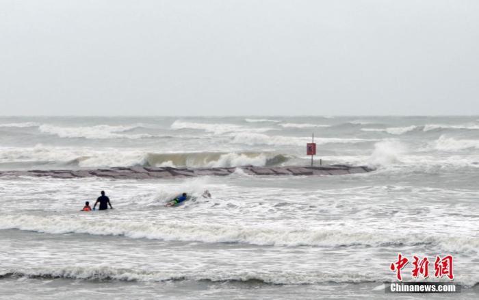 """当地时间8月26日,美国国家飓风中心报告称,""""劳拉""""已于当日增强至""""极其危险的四级飓风"""",预计将于当晚袭击路易斯安那州和得克萨斯州的沿海地区。图为飓风""""劳拉""""来袭前,人们在得州加尔维斯顿岛海边冲浪。日前岛上居民被要求强制撤离。<em></em> 中新社记者 曾静宁 摄"""