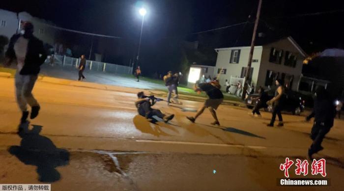 资料图:当地时间8月25日,美国威斯康星州基诺沙,在非裔男子布莱克遭警察多次开枪射击引发示威抗议中,一名男子举枪射击。