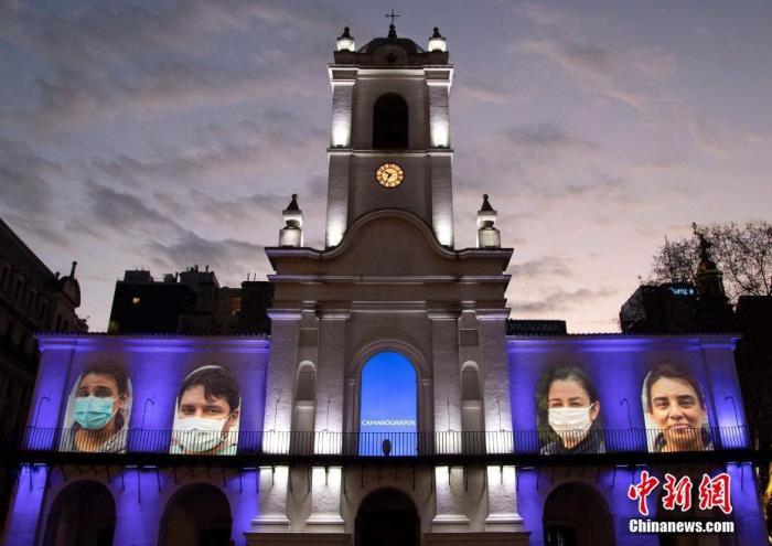 当地时间2020年8月29日,阿根廷布宜诺斯艾利斯,抗疫一线工作人员的肖像被投射在历史悠久的布宜诺斯艾利斯小屋上,以表达对他们的敬意。 图片来源:人民视觉