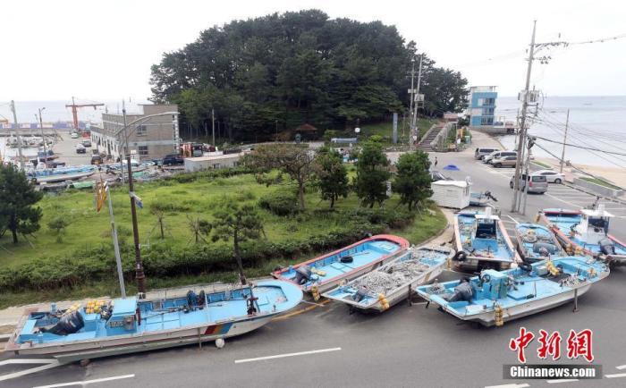 """当地时间8月31日,韩国釜山,台风""""美莎克""""来袭,渔船被撤离到路边。今年第9号台风""""美莎克""""(强台风级)8月31日8时位于距离日本冲绳县那霸市南偏东方向约425公里的西北太平洋洋面上,预计""""美莎克""""将向北偏西方向移动,强度逐渐增强,将于9月1日凌晨移入东海东南部,强度最强可达超强台风级。图片来源:人民视觉"""