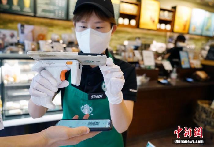 9月1日,韩国首尔市钟路区一家连锁咖啡厅内,工作人员对出入人员进行扫码登记。自8月以来,韩国确诊病例激增,韩国政府升级了首都圈防疫管控,连锁咖啡厅目前禁止堂食,仅允许外带、外卖服务。 中新社记者 曾鼐 摄