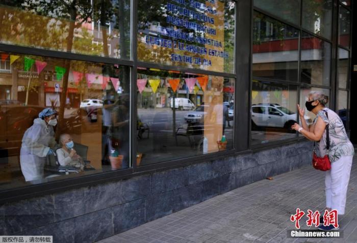 当地时间9月2日,西班牙巴塞罗那,一家养老院将老人推到玻璃窗前与前来探望的亲朋好友见面。