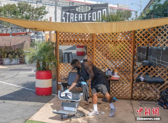 当地时间9月6日,美国旧金山理发师布赖斯清理设在户外的理发设备。近日,旧金山理发、按摩和美甲等行业的从业者获准在户外为顾客提供服务。<em></em> 中新社记者 刘关关 摄