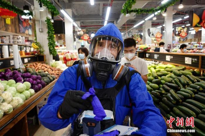 当地时间9月7日,一位市民身着防护服头戴防护面具在纽约皇后区一家超市为顾客发手套、口罩等抗疫物资。美国约翰斯・霍普金斯大学7日发布的新冠疫情最新统计数据显示,美国累计确诊病例已超过629万例。 中新社记者 廖攀 摄