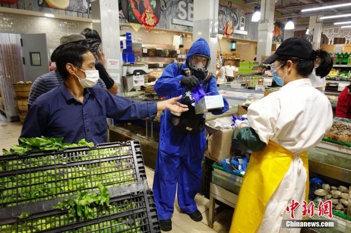 当地时间9月7日,一位市民身着防护服头戴防护面具在纽约皇后区一家超市为顾客发手套、口罩等抗疫物资。美国约翰斯·霍普金斯大学7日发布的新冠疫情最新统计数据显示,美国累计确诊病例已超过629万例。 /p中新社记者 廖攀 摄