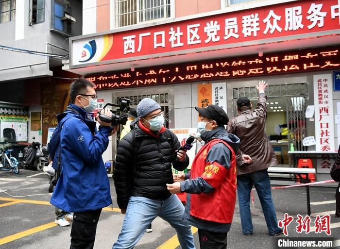 """9月8日,全国抗击新冠肺炎疫情表彰大会在北京人民大会堂举行。身为投入这场抗疫斗争的新闻工作者中一员,中国新闻社青年记者杨程晨作为中新社战疫报道群体的代表,受表彰为""""全国抗击新冠肺炎疫情先进个人""""。资料图为3月3日,湖北武汉,杨程晨采访黄鹤楼街道的社区工作者。 中新社记者 安源 摄"""