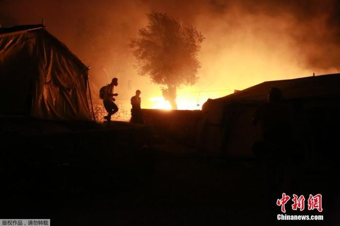 当地时间9月9日,希腊莱斯博斯岛的莫里亚难民营发生大火后,难民离开着火地。据报道,该难民营中人数超过1.2万人,起火原因暂不清楚。一名希腊警察表示,难民营内的人已被转移至安全地点。
