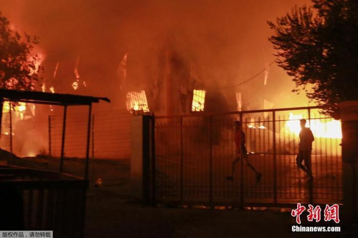 当地时间9月9日,希腊莱斯博斯岛的莫里亚难民营发生大火后,难民离开着火地。