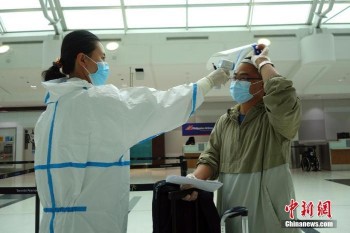 當地時間9月9日,加拿大多倫多皮爾遜國際機場,海南航空公司工作人員對準備搭乘航班直飛北京的乘客檢測體溫。 <a target='_blank' href='http://www.xinshangren.com.cn/'>中新社</a>記者 余瑞冬 攝