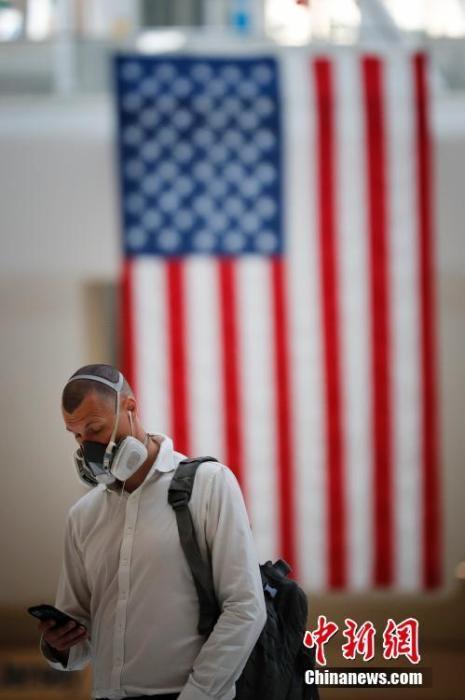 """当地时间9月11日,纽约世贸中心车站悬挂巨幅美国国旗,一名乘客头戴防护面具从国旗下走过。当日,美国""""9·11""""恐怖袭击事件19周年纪念活动在纽约""""9·11""""遗址纪念广场举行。 <a target='_blank' href='http://fl923.com/'>中新社</a>记者 廖攀 摄"""