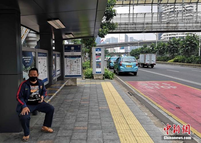 资料图:图为一印尼市民佩戴口罩在公交停靠站候车。 中新社记者 林永传 摄