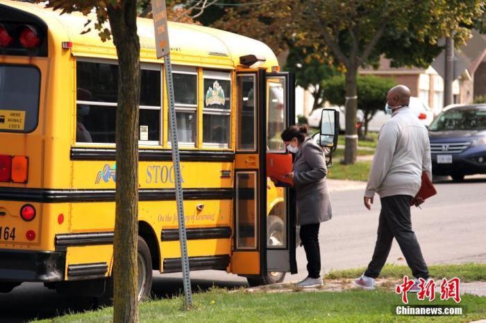 当地时间9月15日,加拿大多伦多一所小学的教职工向校车司机核对接载学生的信息。按照防疫计划,多伦多公校教育局下属的小学从这一天开始连续三天分批次开学,恢复课堂教学。多伦多公校教育局旗下现有583所中小学,为24.7万名中小学生提供服务,是加拿大规模最大的公校教育局。 中新社记者 余瑞冬 摄