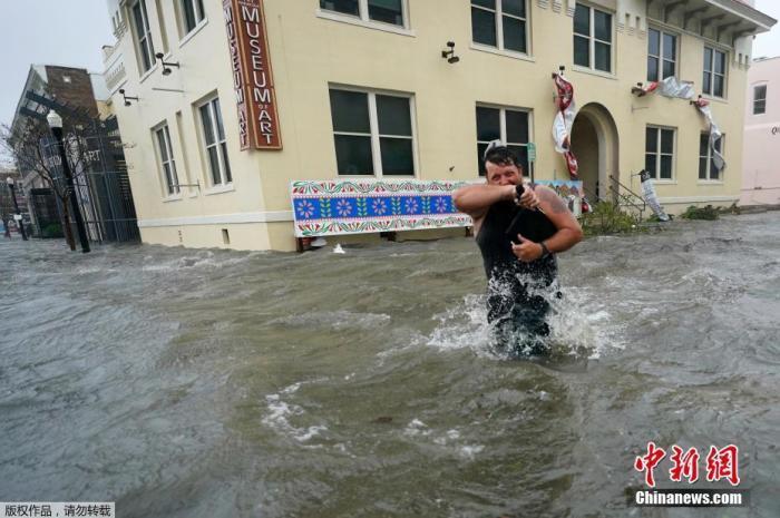 图为佛罗里达潘汉德尔民众蹚水出行。