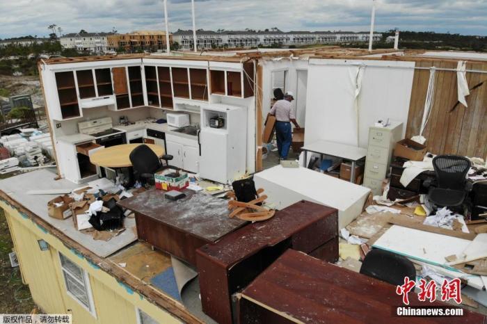 """当地时间9月17日,在美国佛罗里达州Perdido Key,当地一家企业的房屋在飓风""""萨利""""过境时被损毁,一片狼藉。图为工作人员清理受灾现场。"""