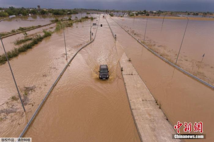 """当地时间9月19日,希腊阿特塞亚诺村附近的一辆汽车在洪水泛滥的高速公路行驶。据报道,截至当地时间9月18日下午,希腊多地已经受到气旋风暴""""伊亚诺斯""""的强烈影响,局部地区出现了大面积停电、洪水、学校停课和轮渡停航。"""