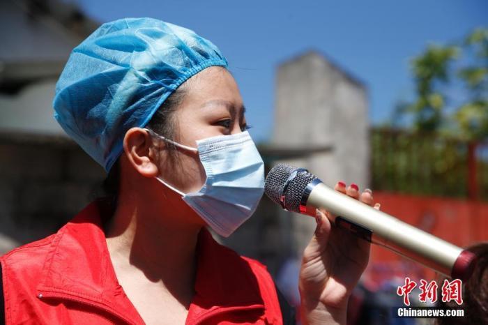 图为曾莉在村子中进行疫情防控宣传。 中新社记者 蒋启明 摄
