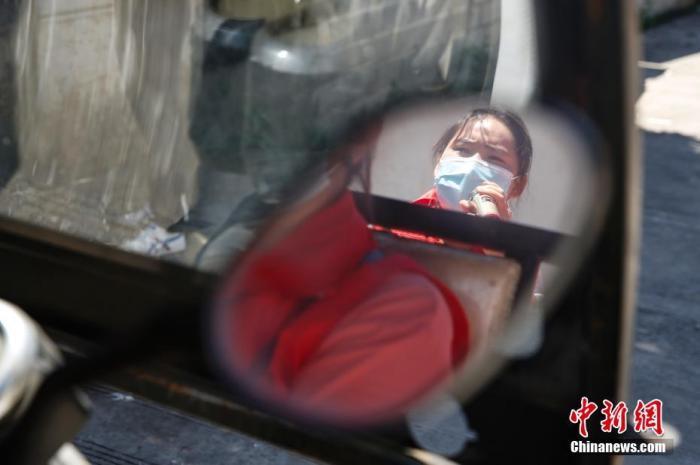 图为缅籍华人志愿者李秋英在村子中进行疫情防控宣传。 中新社记者 蒋启明 摄