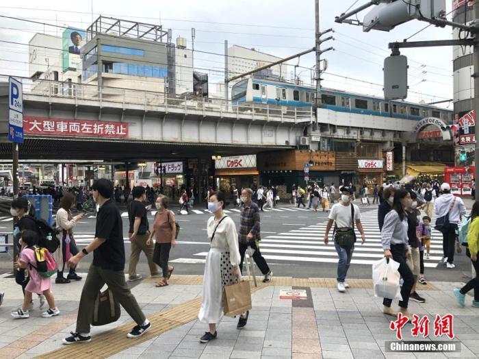 当地时间9月20日为日本四连休小长假的第二天,外出民众明显增多。图为东京街头戴口罩出行的民众。 中新社记者 吕少威 摄