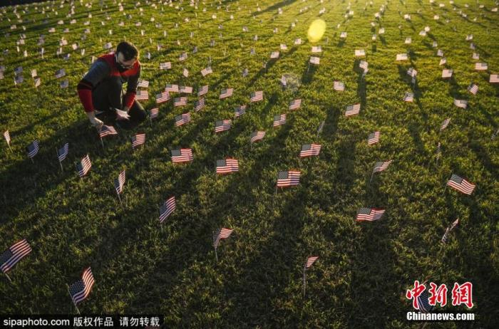 当地时间9月21日,美国华盛顿,志愿者在国家广场上放置2万面美国国旗,纪念新冠肺炎疫情里死亡的近20万人。图片来源:Sipaphoto版权作品 禁止转载