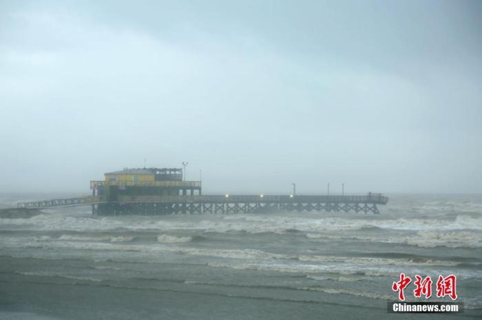 """当地时间9月21日,美国国家飓风中心的数据显示,热带风暴""""贝塔""""预计于当晚在美国休斯敦市西南100英里处的马塔哥达湾登陆,将给得克萨斯州东南部地区带来强降雨。图为当日上午,加尔维斯顿岛61号码头的部分甲板和栏杆被海浪冲断。 中新社记者 曾静宁 摄"""