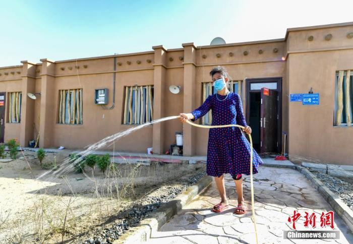 """资料图:9月21日,新疆和田地区于田县达里雅布依乡易地扶贫搬迁安置点,村民用自来水给自家房前种植的小树苗浇水。达里雅布依乡,因地处塔克拉玛干沙漠腹地,被誉为""""中国最后的沙漠部落""""。新建设的达里雅布依乡易地扶贫搬迁安置点距离县城90公里,2017、2019年分两批共计搬迁建档立卡贫困户216户839人。安置点现已通水、通电、通路、通广播电视、通宽带,并配套建设有水厂、卫生院、小学、幼儿园等设施,村民通过转移就业、种植大芸、发展养殖等脱贫增收,步入了崭新的现代化生活。 /p中新社记者 刘新 摄"""
