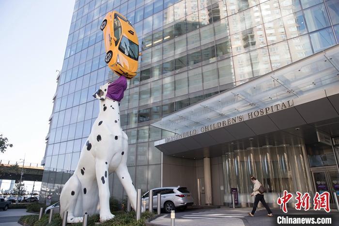 当地时间9月21日,纽约曼哈顿一座斑点狗顶起出租车的巨型雕塑,其中的斑点狗被人戴上了巨型口罩。 中新社记者 廖攀 摄