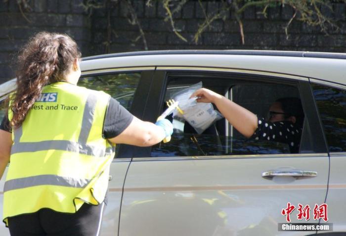 资料图:英国伦敦一核酸检测人员隔着车窗收取受检者的受检生物样本。 中新社发 高天胤 摄