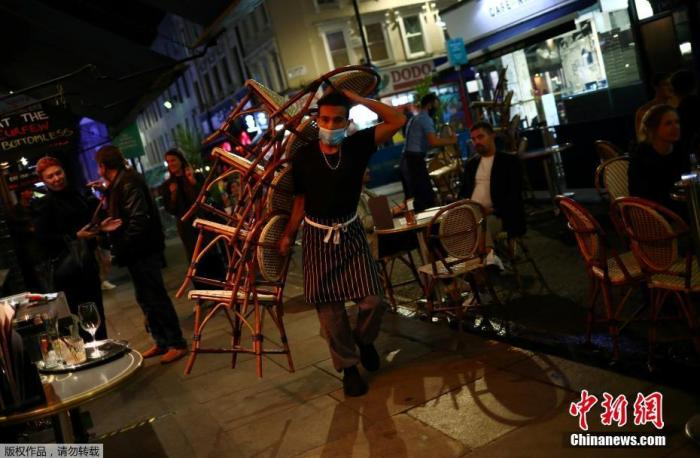 当地时间9月24日,英国伦敦,一家饭店的服务生在收拾桌椅。