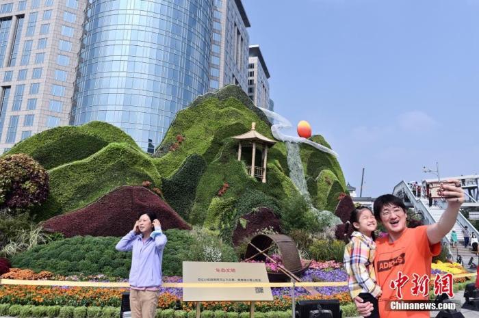 资料图:市民在北京东单国庆主题花坛前自拍留影。中新社记者 张兴龙 摄