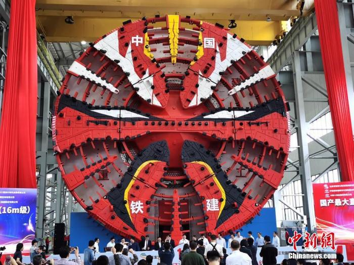 """9月27日,一台最大开挖直径达16.07米的超大直径盾构机在湖南长沙下线,这是中国迄今研制的最大直径盾构机。该盾构机由中国铁建重工集团股份有限公Ū中铁十四局集团有限公司联合研制,是中国企业首次成功实现16米级超大直径盾构机的工业制造。这台""""巨无霸""""设备整机长150米,总重量4300吨,犹如一条钢铁巨龙横卧车间,刀盘涂装以¶剧中的红色脸谱��设计原型。设备取名""""¶华,出厂后将参与北¶东六环攻工程建设。 a target='_blank' href='http://www.chinanews.com/'中新社/a记者 向一鹏 摄"""