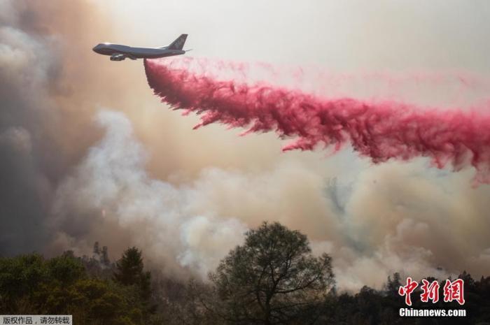 图为当地出动飞机撒红色阻燃剂灭火。