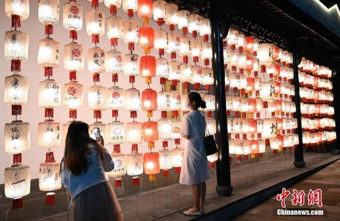 资料图:两名游客在杭州河坊街的灯笼前拍照留影。 <a target='_blank' href='http://www.chinanews.com/'>中新社</a>记者 张茵 摄