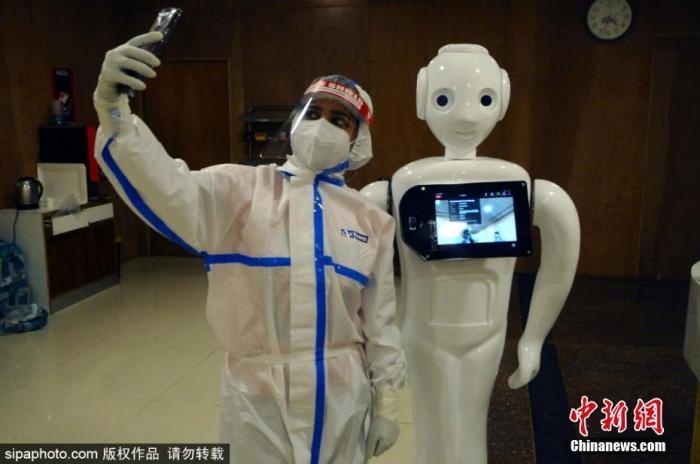 当地时间9月28日,印度诺伊达,印度北方邦(Uttar Pradesh)的Yathartha医院用机器人帮助患者与外界联系,图为医护人员与机器人合影。图片来源:Sipaphoto 版权作品 请勿转载