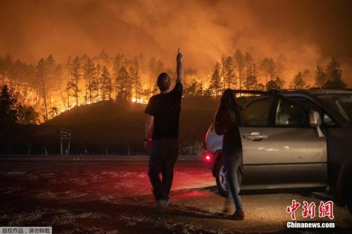 当地时间9月28日,美国加州卡利斯托加市,山火持续肆虐。图为当地民众眺望远处山林大火。