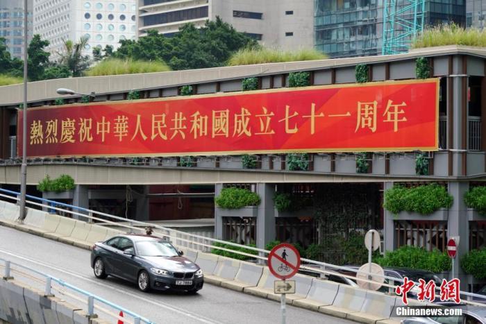 9月30日,香港街头洋溢着浓浓的国庆节日气氛,庆祝中华人民共和国成立71周年的标语、广告、宣传画等随处可见。图为位于香港中环的巨幅庆祝标语。 中新社记者 张炜 摄