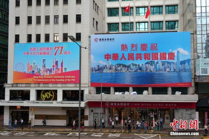 9月30日,香港街头洋溢着浓浓的国庆节日气氛,庆祝中华人民共和国成立71周年的标语、广告、宣传画等随处可见。图为位于香港中环的巨型庆祝广告。 中新社记者 张炜 摄