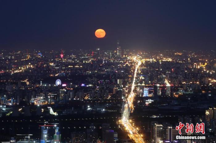 """10月2日,中秋国庆假期第二天,北京天气晴好,一轮明月在夜晚逐渐升起。当日是农历八月十六,中国民间有""""十五月亮十六圆""""的说法。<a target='_blank' href='http://www.hsliebao.com/'>中新社</a>记者 盛佳鹏 摄"""