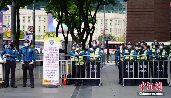 """資料圖:10月3日,韓國多個民間團體發起""""免下車""""集會,首爾調動大批警力嚴防疫情。圖為大批警察在首爾光化門廣場附近設置路障,禁止隨意出入;路上貼有通知,稱根據傳染病相關法規,禁止集會,違者將被處以罰款。 <a target='_blank' href='http://www.gsghx.cn/'>中新社</a>記者 曾鼐 攝"""