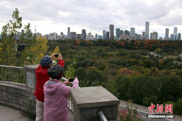 """当地时间10月3日,加拿大多伦多两位市民在一处观景台拍摄秋意渐浓的城市。有""""枫叶之国""""美誉的加拿大正迎来美丽的金秋时节。 中新社记者 余瑞冬 摄"""