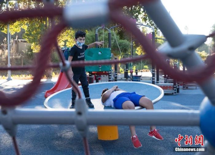 当地时间10月4日,美国北加州圣马特奥市儿童在一处游乐场玩耍。在遵守防疫准则的前提下,全加州范围内因新冠疫情被关闭的户外游乐场所近期获准重开,各地可根据实际情况决定重开时间。<em></em> 中新社记者 刘关关 摄