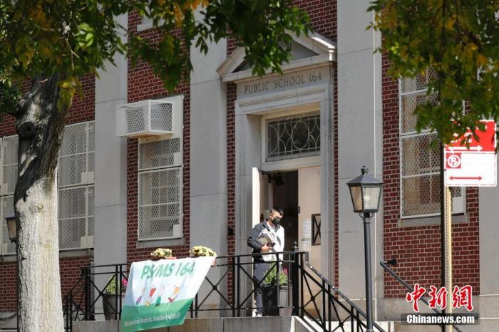 当地时间10月6日,纽约市皇后区的一所公立学校门前,一名男子从关闭的学校中取走书籍。当日,纽约市部分地区的学校开始关闭,以防止新冠疫情继续扩散。近期,纽约市布鲁克林区和皇后区部分区域出现新冠肺炎聚集性传染。 中新社记者 廖攀 摄