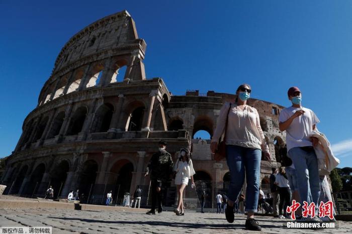 当地时间10月8日,意大利首都罗马,民众佩戴口罩走过斗兽场。