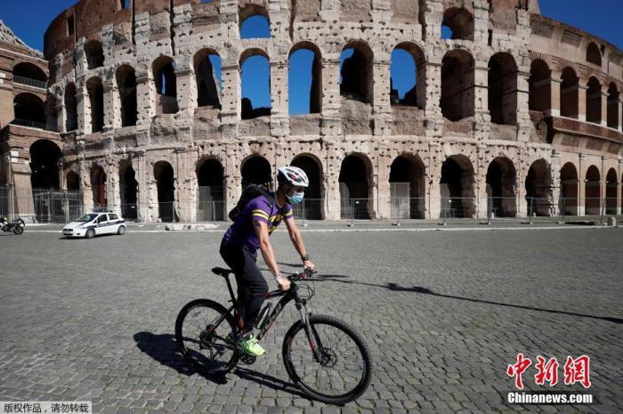 资料图:当地时间10月8日,意大利首都罗马,一男子佩戴口罩骑车经过斗兽场。