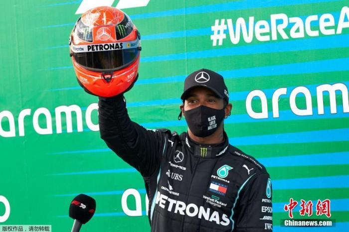 汉密尔顿高高举起车王舒马赫的红色头盔,向传奇致敬。