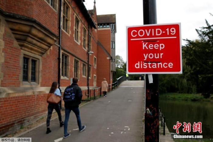资料图:当地时间10月12日,英国剑桥,道路旁挂着提醒人们保持社交距离的标志。
